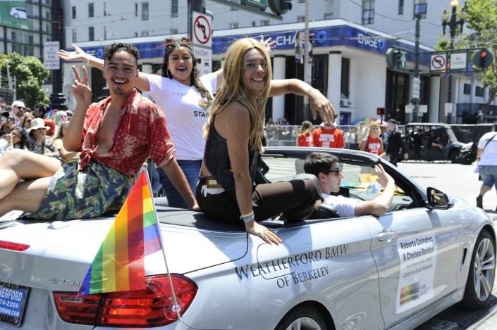 Three smiling LGBTQ Latinos ride along a city street in an open-top convertible with a rainbow flag
