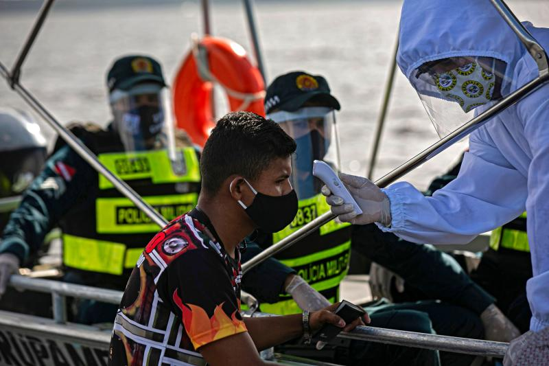 A government medical worker, in a joint operation with military police, checks the temperature of a passenger on a boat in the Melgaco bay, southwest of the island of Marajo, Para state, Brazil, on May 27, 2020. - People onboard small boats, ferries and ships on the river had their body temperature checked as authorities try to combat the new coronavirus. (Photo by TARSO SARRAF / AFP) (Photo by TARSO SARRAF/AFP via Getty Images)