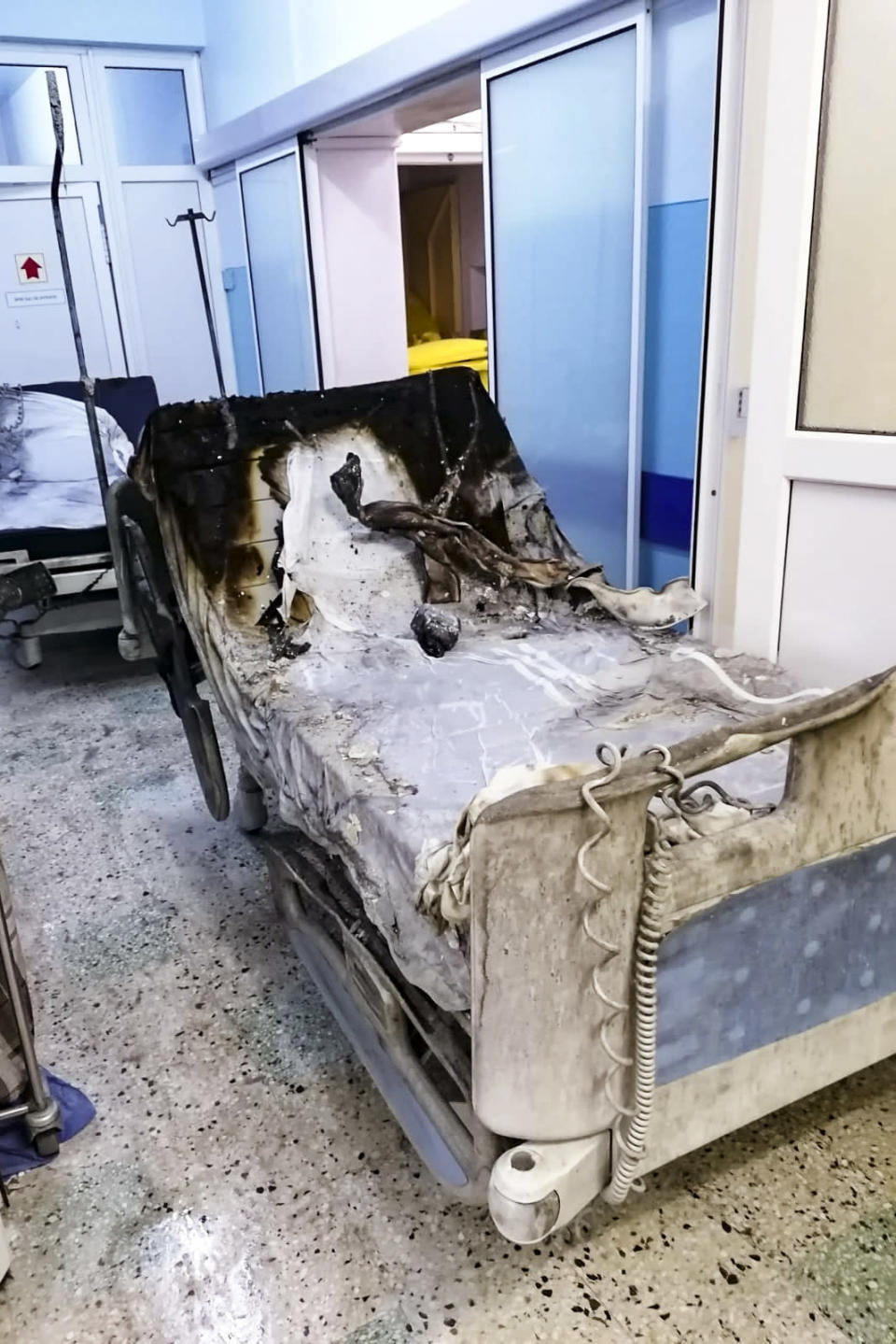 A burned bed from the destroyed COVID-19 intensive care ward at the hospital in Piatra Neamt, northern Romania, Saturday, Nov. 14, 2020, is placed in a corridor after a fire. Romanian officials say a fire at a hospital treating COVID-19 patients has killed 10 people and critically injured seven others as a blaze spread through the intensive care ward designated for people with COVID-19 patients at the public hospital according to the Emergency Situations Inspectorate.(Exploziv TV Neamt via AP)
