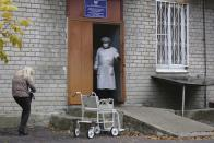 A medical worker stands at an enter of a hospital treating COVID-19 patients in Donetsk, controlled by Russia-backed separatists, Ukraine, Thursday, Oct. 14, 2021. The Russia-backed separatist authorities in eastern Ukraine are reporting the largest spike in new coronavirus infections since the start of the pandemic, saying the health care system has been overwhelmed. The health authorities in the Donetsk region of 2.2 million reported over 1000 new confirmed infections and about hundred coronavirus deaths in the past 24 hours. (AP Photo/Alexei Alexandrov)