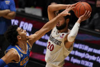 UCLA guard Jules Bernard, left, reaches for the ball as San Diego State guard Jordan Schakel (20) looks to pass it during the first half of an NCAA college basketball game Wednesday, Nov. 25, 2020, in San Diego. (AP Photo/Gregory Bull)