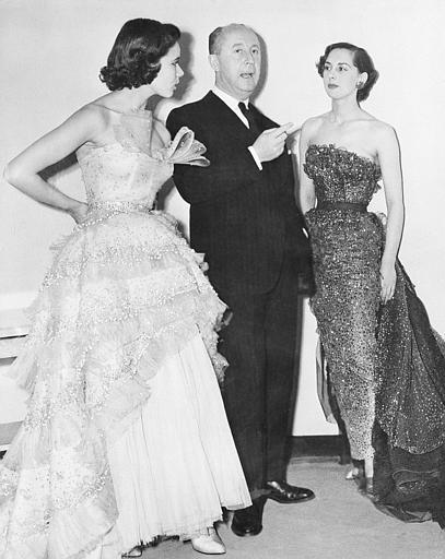 "French fashion designer Christian Dior is seen with two unidentified models displaying his fashion designs at London's Savoy Hotel, April 28, 1950. He calls the creation at left ""Mozart."" Money raised by the showing will go to the fund for a costume museum. (AP Photo/Dennis Lee Royle)"