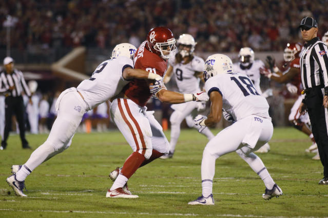 Oklahoma tight end Mark Andrews (81) comes down with a pass between TCU safety Niko Small, left, and safety Nick Orr (18) during an NCAA college football game in Norman, Okla., Saturday, Nov. 11, 2017. Oklahoma won 38-20. (AP Photo/Sue Ogrocki)