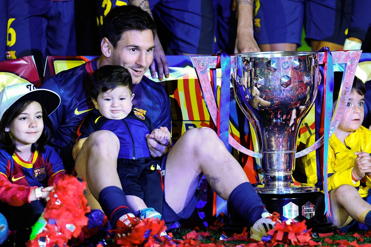 BARCELONA, SPAIN - MAY 19:  Lionel Messi of FC Barcelona holds his son Thiago as they sit next to the trophy  during the celebration after winning the Spanish League  after the La Liga match between FC Barcelona and Real Valladolid CF at Camp Nou on May 19, 2013 in Barcelona, Spain.  (Photo by David Ramos/Getty Images)