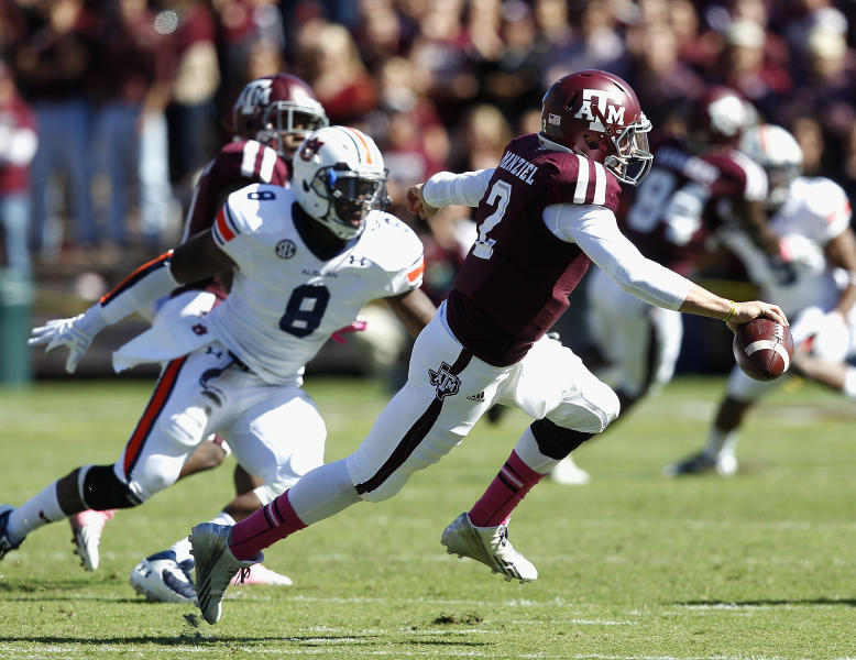 Texas A&M quarterback Johnny Manziel (2) avoids a tackle attempt by Auburn linebacker Cassanova McKinzy (8) in the first quarter during an NCAA college football game Saturday, Oct. 19, 2013, in College Station, Texas. (AP Photo/Bob Levey)