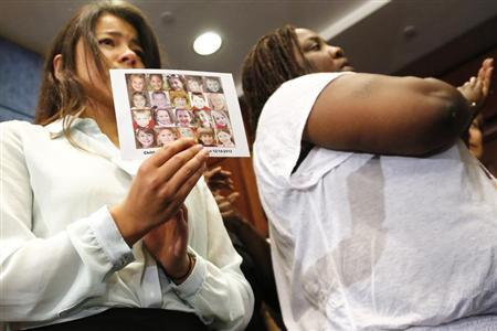 A woman holds a picture of Sandy Hook victims at news conference with family members of gun violence victims at the U.S. Capitol in Washington
