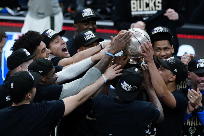 The Milwaukee Bucks hoist the trophy after defeating the Atlanta Hawks in Game 6 of the Eastern Conference finals in the NBA basketball playoffs and advancing to the NBA Championship, Saturday, July 3, 2021, in Atlanta. (AP Photo/John Bazemore)