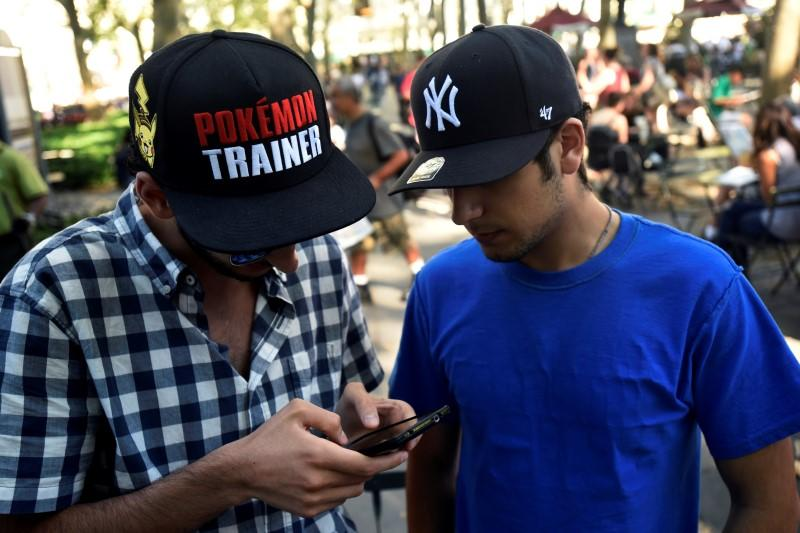 "A man wears a Pokemon-themed hat as he plays the augmented reality mobile game ""Pokemon Go"" by Nintendo in Bryant Park, New York City"