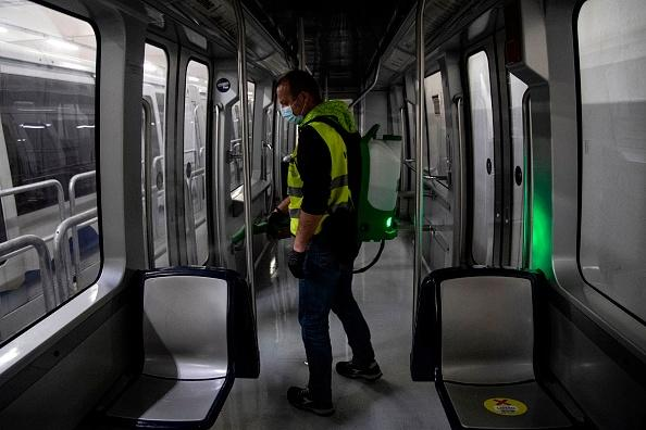 An employee wearing gloves and a protective face mask disinfects inside a Metro train at the Turin Transport Group GTT.