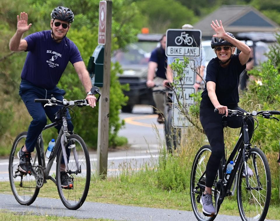 US President Joe Biden (L) and First Lady Jill Biden ride bicycles in Cape Henlopen State Park on June 3, 2021, in Lewes, Delaware. (Photo by JIM WATSON / AFP) (Photo by JIM WATSON/AFP via Getty Images)