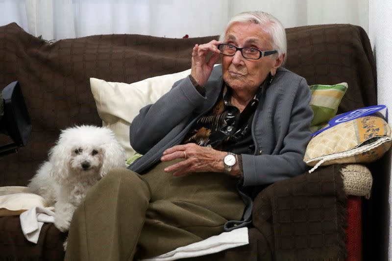 Florentina Martin, a 99 year-old woman who survived coronavirus disease (COVID-19), sits on a sofa with her pet Luna as she watches TV in her home in Pinto