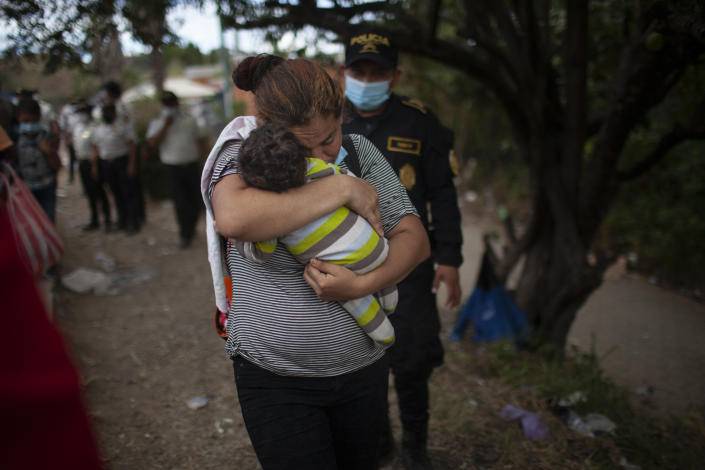 A woman carries her son as Honduran migrants confront Guatemalan soldiers and police manning a roadblock that prevents them from advancing toward the US, on the highway in Vado Hondo, Guatemala, Monday, Jan. 18, 2021. The roadblock was strategically placed at a chokepoint on the two-lane highway flanked by a tall mountainside and a wall leaving the migrants with few options. (AP Photo/Sandra Sebastian)