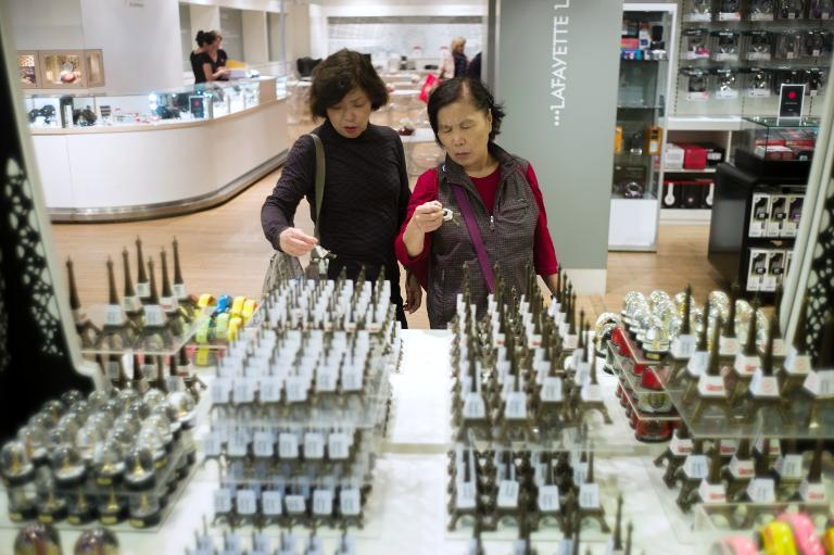 Chinese tourists look at Eiffel Tower souvenir at the Galeries Lafayette shopping center, on October 4, 2012 in Paris