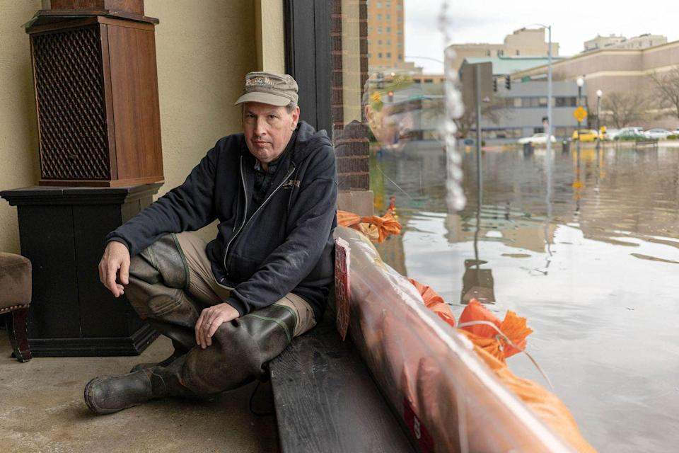 <p>A man rests next to flood waters near the main breach in the Mississippi River in Davenport, Iowa on Friday, May 3, 2018.</p>