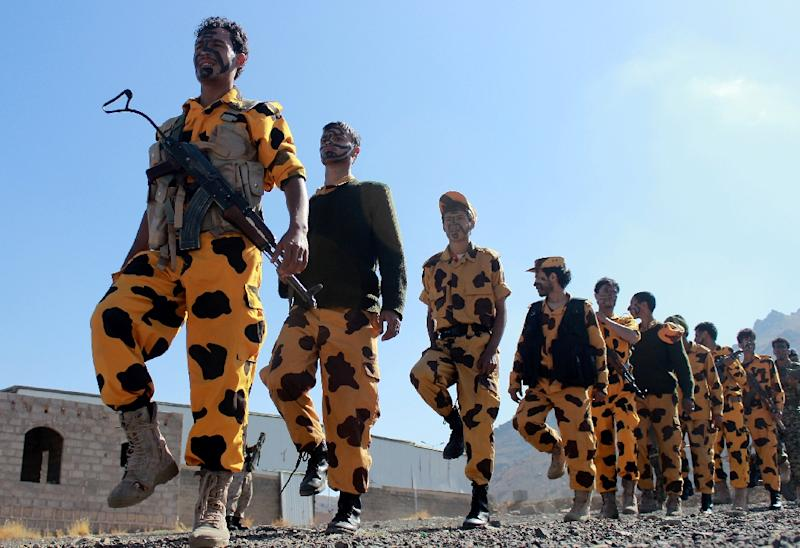 Supporters of Shiite Huthi rebels and militiamen march in yellow camouflage pants at a rally against the Arab coalition on December 14, 2015 in Sanaa (AFP Photo/Abdel Rahman Abdallah)