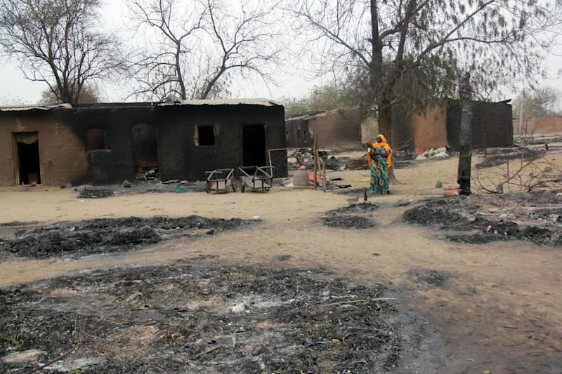 A photo taken on April 21, 2013 shows a woman walking past burnt houses, in Baga