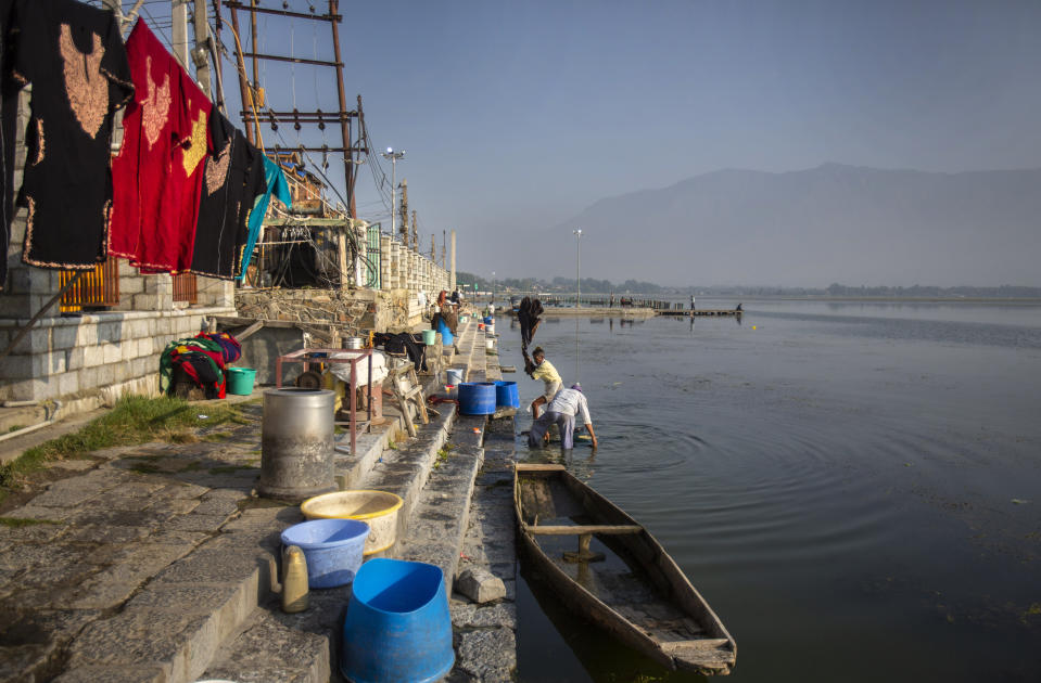 A Kashmiri washerman washes clothes on the banks of Dal lake in Srinagar, Indian controlled Kashmir, Tuesday, Sept. 14, 2021. Weeds, silt and untreated sewage are increasingly choking the sprawling scenic lake, which dominates the city and draws tens of thousands of tourists each year. (AP Photo/Mukhtar Khan)