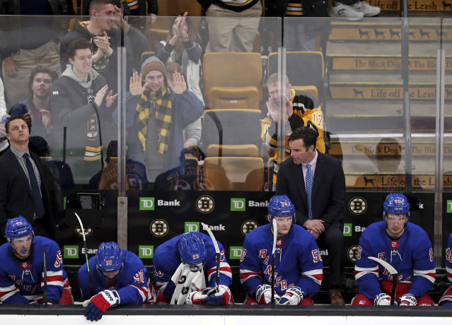 New York Rangers sit as Boston Bruins fans celebrate following a goal by defenseman Charlie McAvoy during the third period of an NHL hockey game in Boston, Wednesday, March 27, 2019. The Bruins won 6-3. (AP Photo/Charles Krupa)
