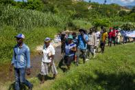 Cholera survivors walk along the Meille River to the former UN base where they will leave flowers as they commemorate 10 years since the cholera outbreak in Mirebalais, Haiti, Monday, Oct. 19, 2020. Ten years after a cholera epidemic swept through Haiti and killed thousands, families of victims still struggle financially and await compensation from the United Nations as many continue to drink from and bathe in a river that became ground zero for the waterborne disease. (AP Photo/Dieu Nalio Chery)