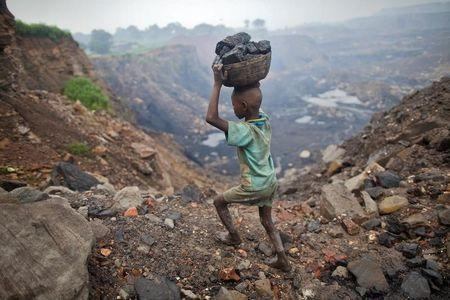 A boy carries coal at an open cast coal field at Dhanbad district in Jharkhand