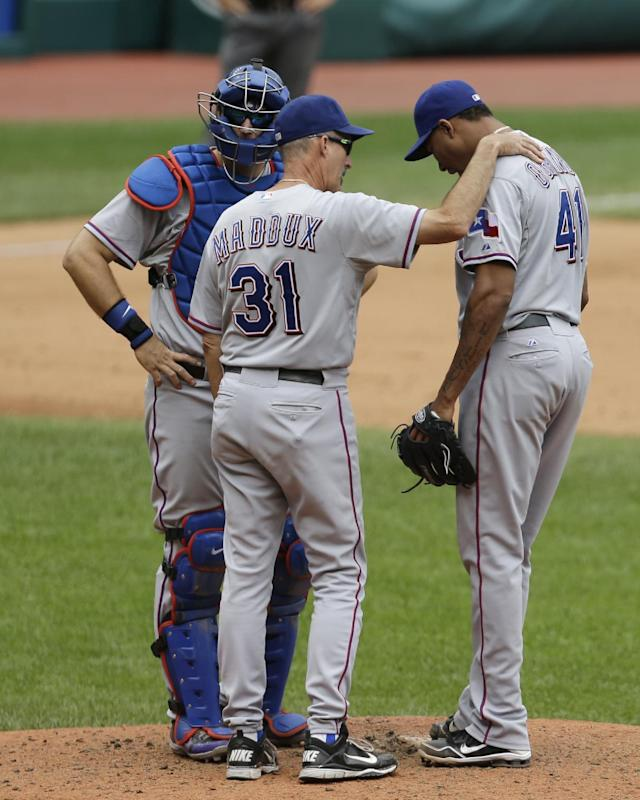Texas Rangers pitching coach Mike Maddux, center, talks with starting pitcher Alexi Ogando, right, as catcher A.J. Pierzynski listens in the fifth inning of a baseball game, Sunday, July 28, 2013, in Cleveland. (AP Photo/Tony Dejak)