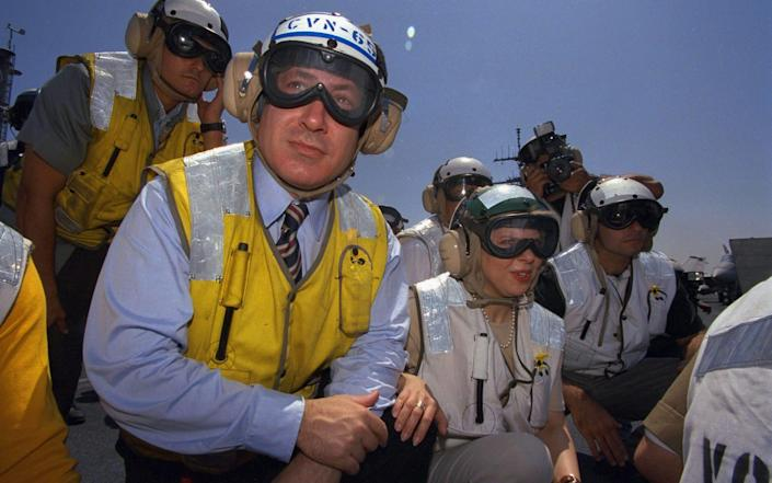 Mr Netanyahu and his wife Sara on the flight deck of the USS Enterprise during a visit to Haifa in 1996 - Hulton Archive