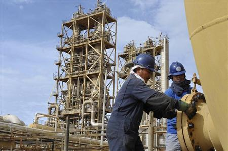 Workers perform maintenance on oil pipelines at the Sirte Oil Company in Brega
