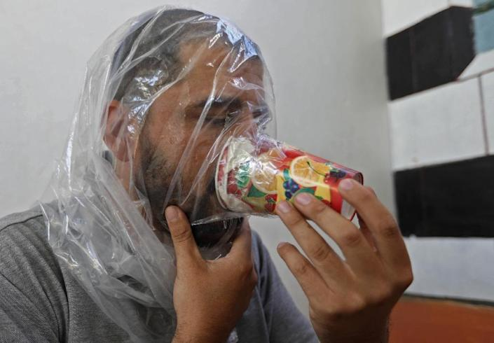 Syrian Hudhayfa al-Shahadh, 27, tries an improvised homemade gas mask as part of preparations for any upcoming raids in the rebel-held Idlib province's village of Maar Shurin, on September 11, 2018. (AFP Photo/OMAR HAJ KADOUR)