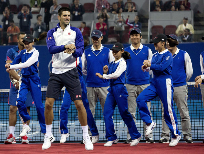 "Serbia's Novak Djokovic, center, performs South Korean rapper PSY's "" Gangnam Style"" dance with volunteers on a court after a prize presentation for the men's singles final match of the China Open tennis tournament in Beijing Sunday, Oct. 7, 2012. Djokovic won the China Open tennis tournament, defeated Jo-Wilfried Tsonga 7-6, 6-2. (AP Photo/Andy Wong)"