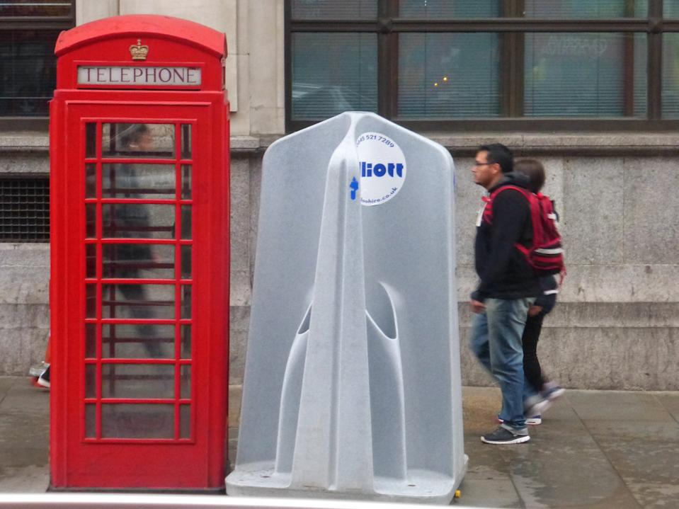Tourists walking past a phone booth and public urinal in London. (Getty)