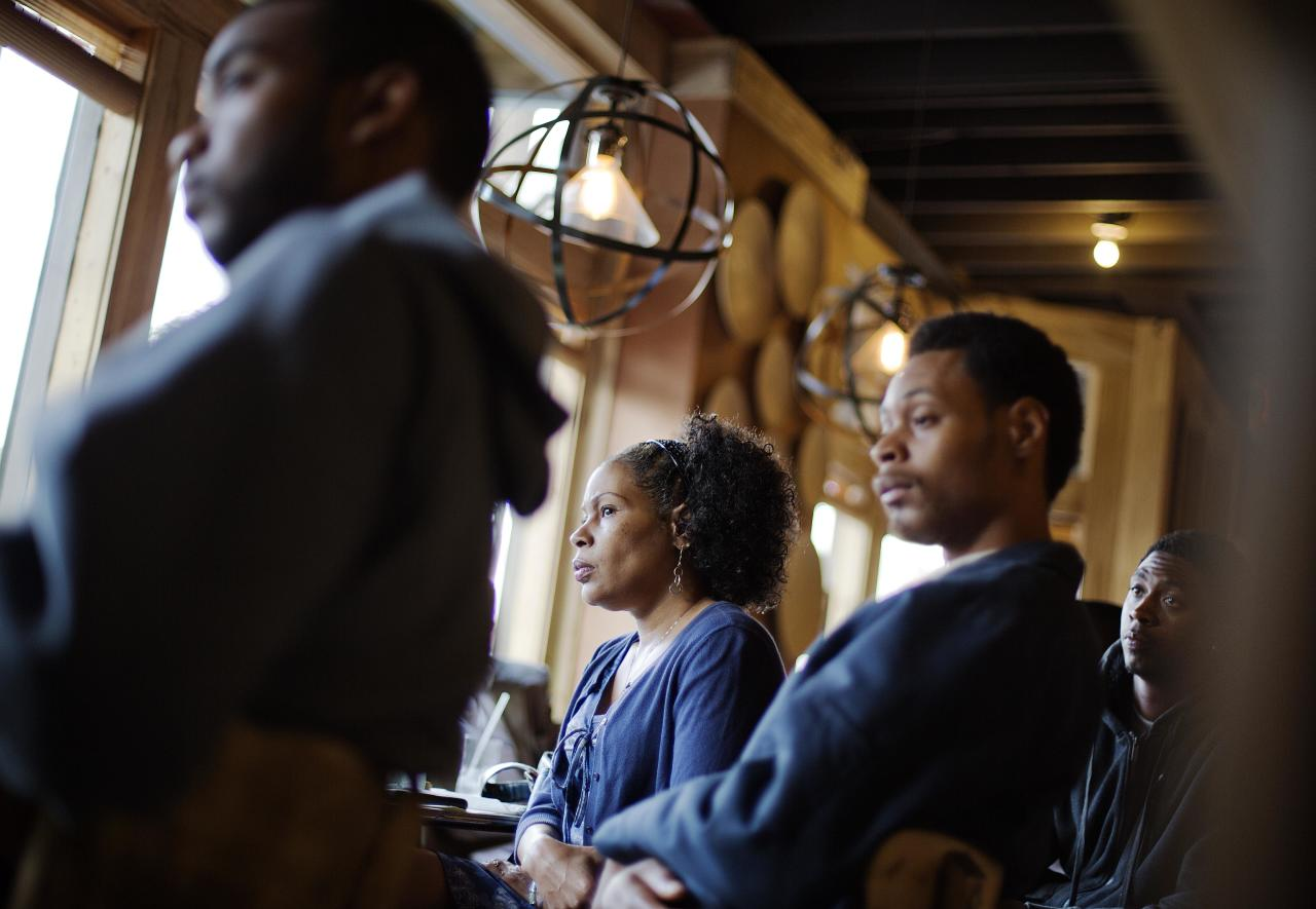 In this photo taken May 18, 2014, Lisa Marie Hyman-Walker, center, and son Eugene Mosby, right, listen to Leo Smith (not shown), minority engagement director for the Georgia Republican Party, speaking at the Delightful Eatz Bar and Grill in the historically African American neighborhood of Edgewood in Atlanta. Smith is on the GOP's front lines recruiting African-American voters in pivotal states. (AP Photo/David Goldman)