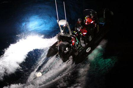 Activists on a rubber dinghy belonging to Sea Shepherd throw a rope onto the bow of the Japanese whaling ship Yushin Maru in the Southern Ocean