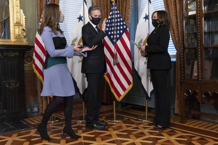 Antony Blinken, center, takes his place to be ceremonially sworn-in by Vice President Kamala Harris, right, before being reminded by his wife Evan Ryan to stand further back, Wednesday, Jan. 27, 2021, in Harris' ceremonial office in the Eisenhower Executive Office Building on the White House complex in Washington. (AP Photo/Jacquelyn Martin)