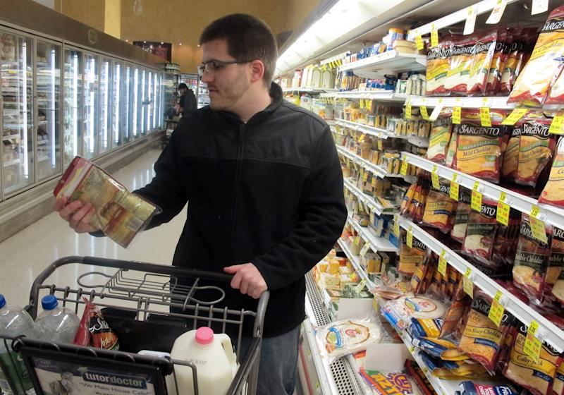 """FILE - In this Dec. 4, 2012 file photo Shopper Ben Rellinger selects shredded cheese and milk at a Milwaukee grocery store. As the nation inches toward the economic """"fiscal cliff,"""" anxiety is growing in farm country about a separate looming deadline, one that reaches into the dairy industry and, indirectly, into the household budgets of consumers who buy milk and cheese. (AP Photo/Dinesh Ramde, File)"""