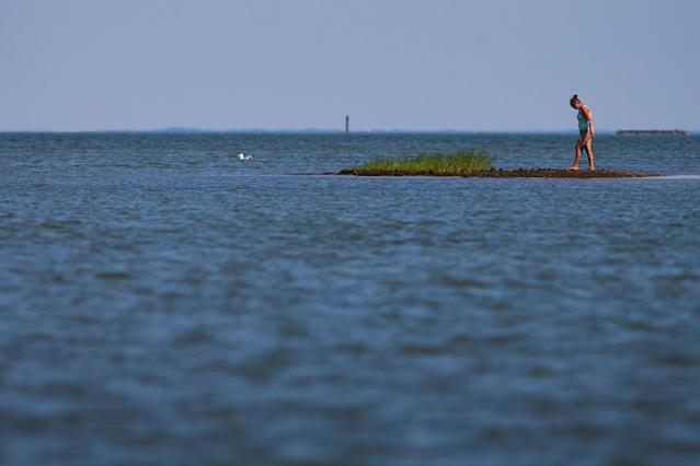 """<p>Brandi Tuck of Yorktown searches for arrowheads in the """"Uppards"""" part of Tangier Island, Virginia, Aug. 2, 2017. (Photo: Adrees Latif/Reuters) </p>"""