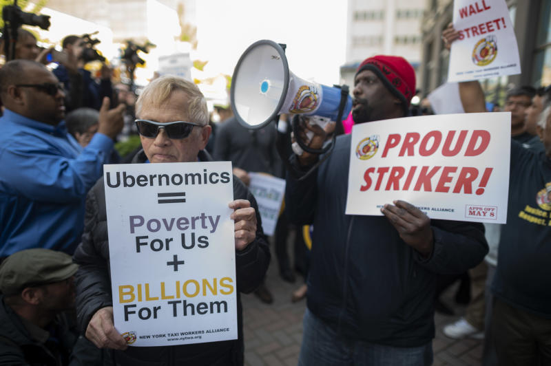 "Drivers take part in a rally demanding more job security and livable incomes, at Uber and Lyft New York City Headquaters on May 8, 2019. - Rideshare drivers in major US cities were set to stage a series of strikes and protests Wednesday, casting a shadow over the keenly anticipated Wall Street debut of sector leader Uber. The app drivers for Uber, Lyft, Via and other platforms are seeking improved job security, including an end to arbitrary ""deactivations,"" and a better revenue split between drivers and platforms. (Photo by Johannes EISELE / AFP) (Photo credit should read JOHANNES EISELE/AFP via Getty Images)"