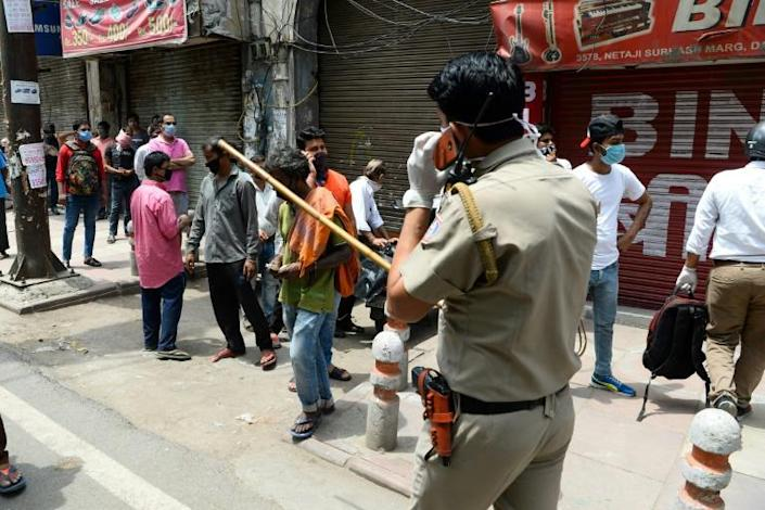 "In Delhi and other Indian cities police liberally swung ""lathi"" batons -- long hardened bamboo canes -- to control crowds outside liquor stores (AFP Photo/Sajjad HUSSAIN )"