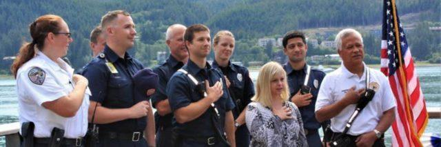 Ashley Deramus and police officers with hand over heart for National Anthem