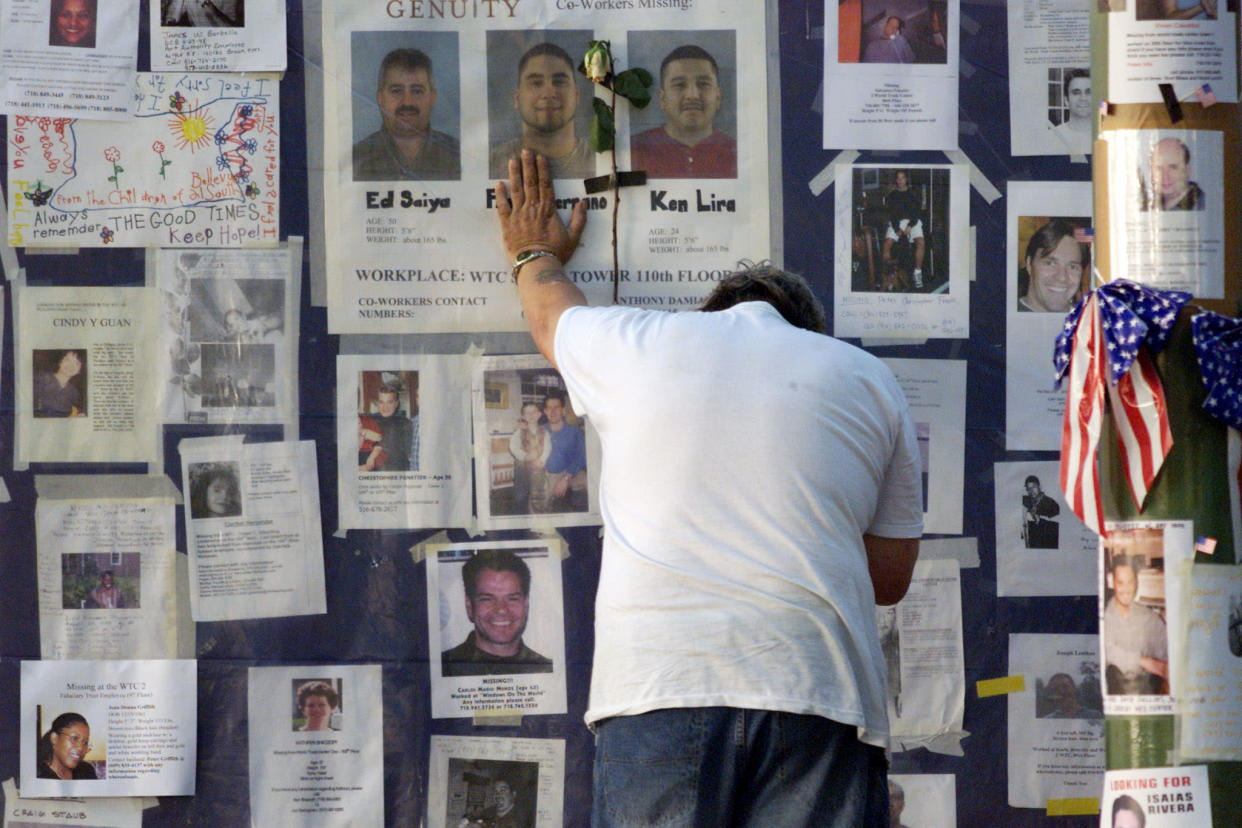 A man places his hand on a wall showing photos of missing people outside Bellevue Hospital in New York September 16, 2001. Family and friends of people missing since the collapse of the World Trade Center have been posting photos of their loved ones. (Russell Boyce/Reuters)