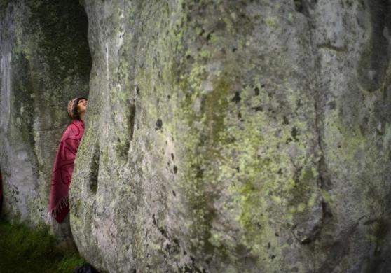 A reveler looks up between the stones during the summer solstice at the ancient Stonehenge monument on Salisbury plain in southern England June 21, 2012.