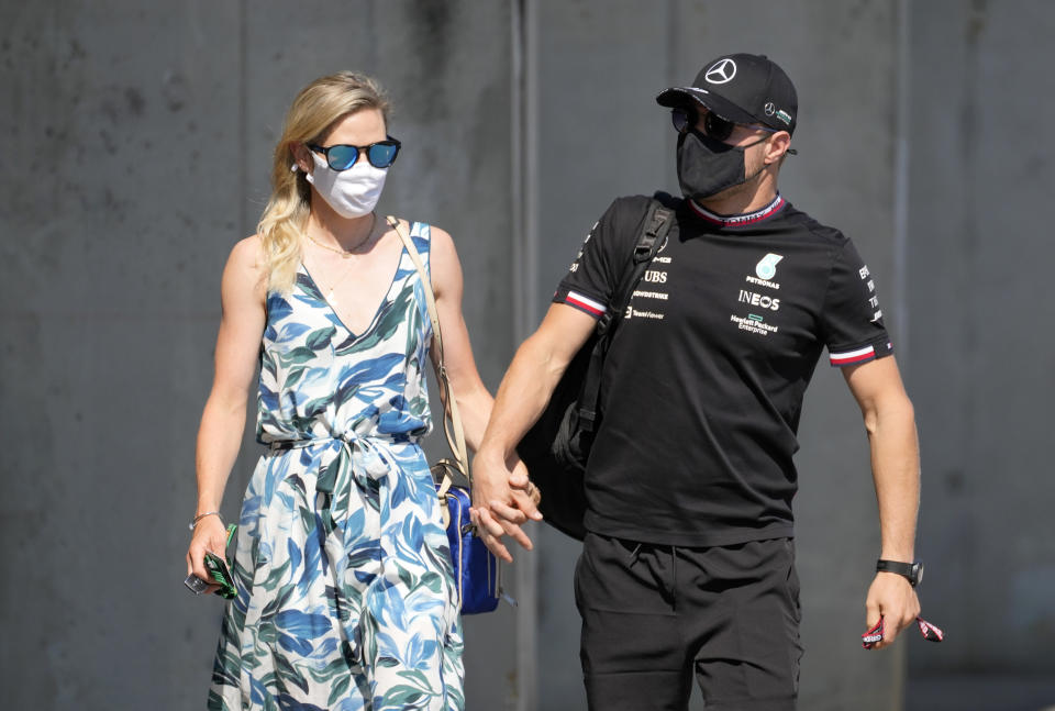 Mercedes driver Valtteri Bottas of Finland, right, with his girlfriend Tiffany Cromwell arrives at the Hungaroring racetrack ahead of the first free practice, in Mogyorod, Hungary, Friday, July 30, 2021. The Hungarian Formula One Grand Prix will be held on Sunday. (AP Photo/Darko Bandic)