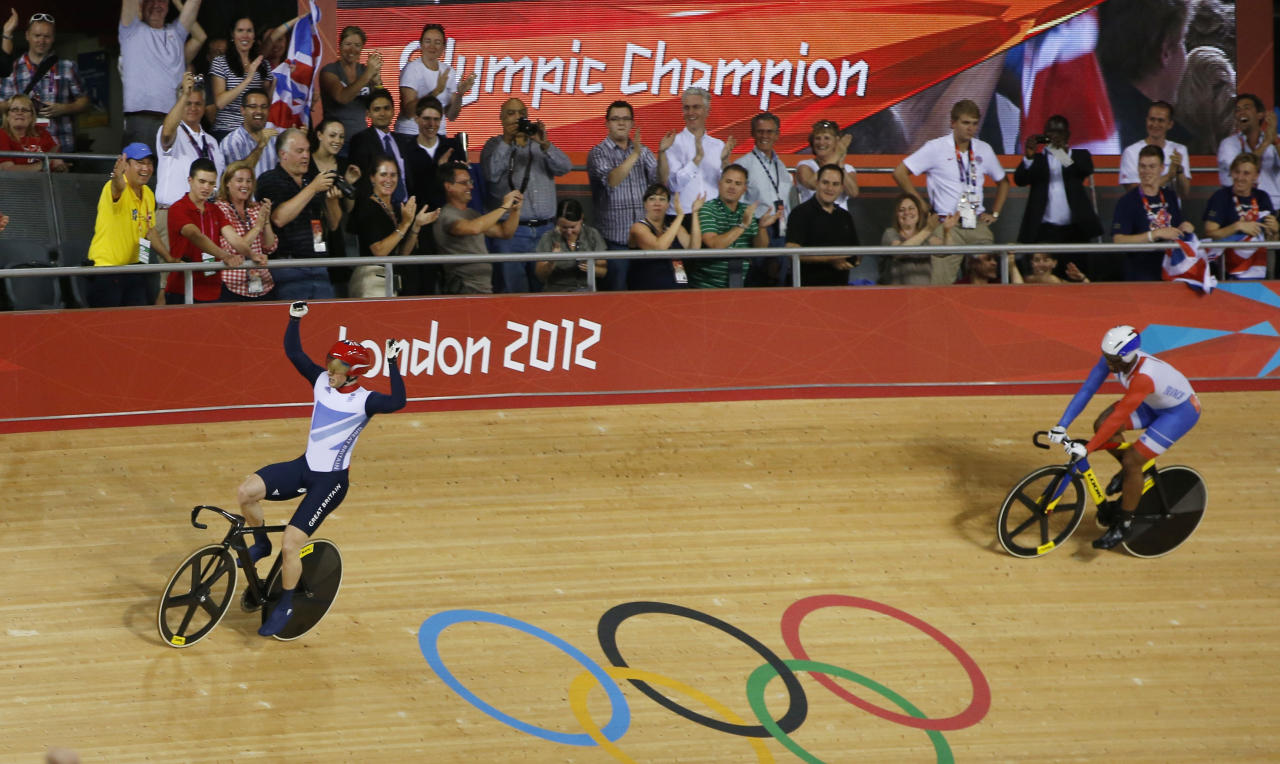 Britain's Jason Kenny (red helmet) celebrates defeating France's Gregory Bauge during the track cycling men's sprint gold finals at the Velodrome during the London 2012 Olympic Games August 6, 2012. Kenny won 2 runs to win the gold medal.          REUTERS/Paul Hanna (BRITAIN  - Tags: OLYMPICS SPORT CYCLING)
