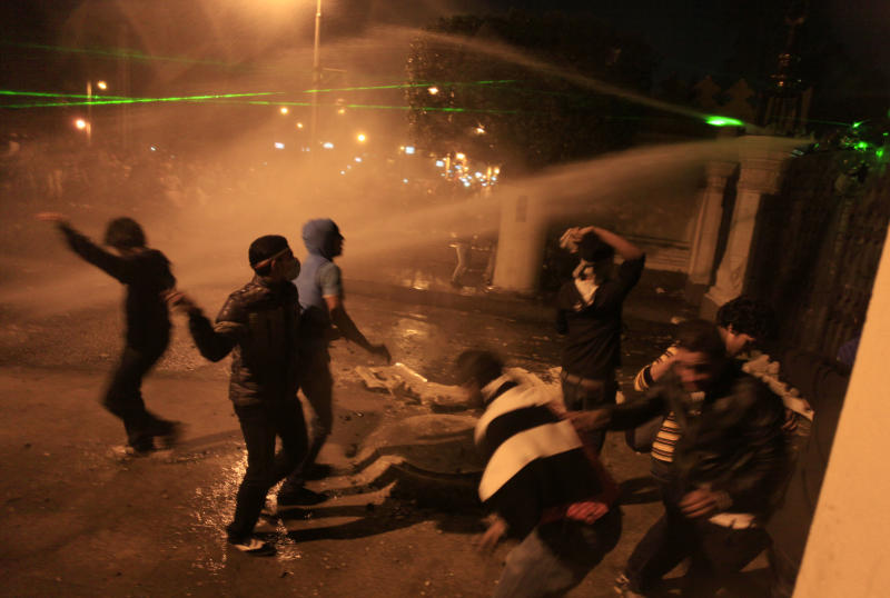 Egyptian protesters throw stones while security police open water canons on them from inside the grounds of the presidential palace during a demonstration in Cairo, Egypt, Friday, Feb. 8, 2013. Egypt has witnessed a fresh cycle of violence over the past two weeks since the second anniversary of the 2011 uprising that deposed longtime autocrat Hosni Mubarak, with clashes across the country having left scores dead and hundreds injured.  (AP Photo/Khalil Hamra)