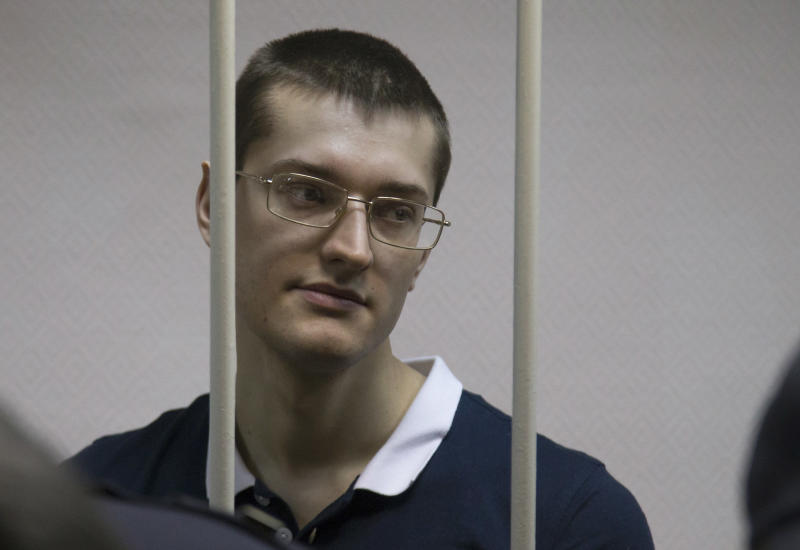 A defendant stands behind bars in a cage at a court room in Moscow, Russia, Monday, Feb. 24, 2014, where hearings started against opposition activists detained on May 6, 2012 during a rally at Bolotnaya Square. A Moscow judge on Friday, Feb. 21, 2014, convicted eight anti-government protesters of rioting during a 2012 protest against Vladimir Putin, following a trial seen as part of the Kremlin's efforts to stifle dissent. (AP Photo/Alexander Zemlianichenko)