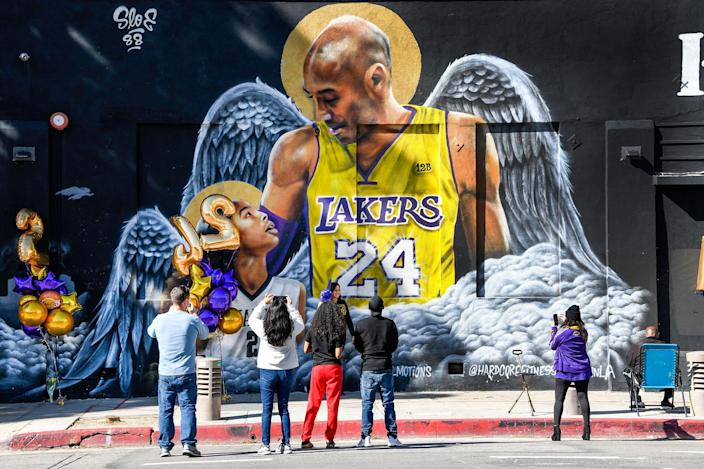 Fans gather at a mural of Kobe Bryant and his daughter Gianna painted on the wall of Hardcore Fitness Bootcamp gym in downtown Los Angeles on Jan 26, 2021. Bryant, his daughter and 7 others died in a helicopter crash in Calabasas, Calif. on Jan. 26, 2020.