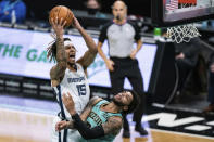 Memphis Grizzlies forward Brandon Clarke (15) fouls Charlotte Hornets forward Miles Bridges during the second half of an NBA basketball game in Charlotte, N.C., Friday, Jan. 1, 2021. (AP Photo/Jacob Kupferman)