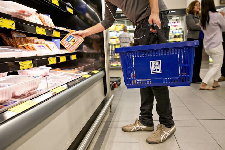 A man picks up a grocery item while shopping in ALDI and carrying a basket.