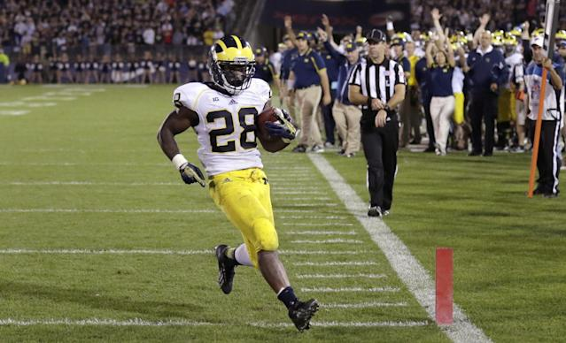 Michigan running back Fitzgerald Toussaint crosses the goal line on his fourth-quarter touchdown against Connecticut in an NCAA college football game, Saturday, Sept. 21, 2013, in East Hartford, Conn. Michigan won 24-21. (AP Photo/Charles Krupa)