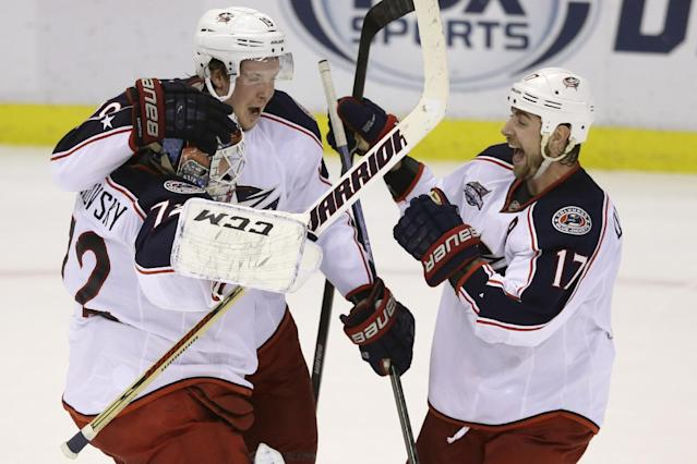 Columbus Blue Jackets goalie Sergei Bobrovsky, left, is congratulated by center Ryan Johansen (19) and center Brandon Dubinsky (17) after the shootout period of an NHL hockey game against the Detroit Red Wings in Detroit, Tuesday, Dec. 16, 2014. The Blue Jackets defeated the Red Wings 1-0. (AP Photo/Carlos Osorio)
