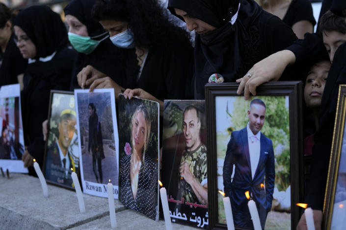 Relatives of victims of the Aug. 4, 2020, Beirut port explosion light candles and hold portraits of their loved ones, in Beirut, Lebanon, Sunday, July 4, 2021. A year after the deadly blast, families of the victims are consumed with winning justice for their loved ones and punishing Lebanon's political elite, blamed for causing the disaster through their corruption and neglect. (AP Photo/Hassan Ammar)